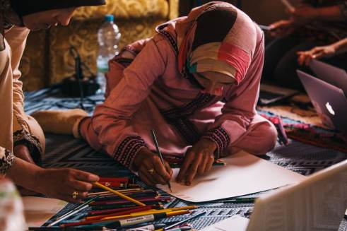 A woman using colored pencils for the first time at Imelghas Cooperative. Photo by Simon Mills.