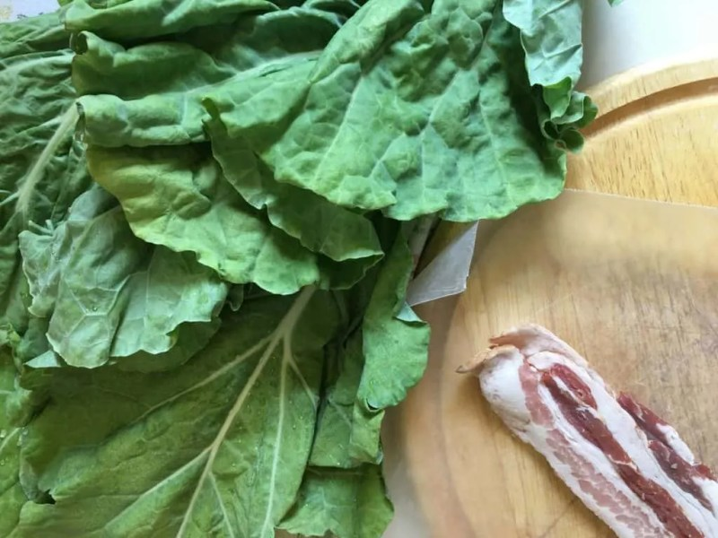 fresh collard greens and bacon on wooden cutting board