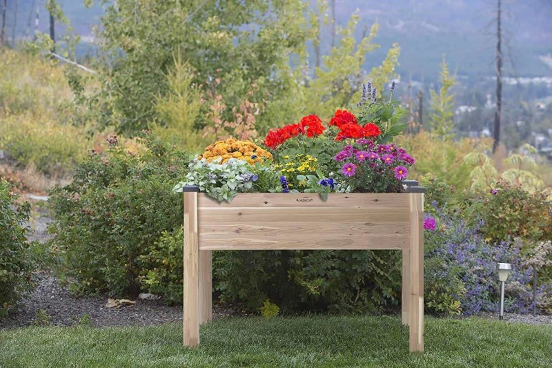 CedarCraft raised planter in a green lawn with flowers