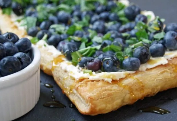 Crispy tart topped with honey, fresh blueberries and chopped basil on a dark counter with a white ramekin of blueberries on the side.