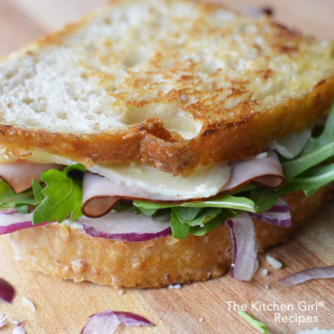 Grilled cheese for grown ups! Sliced sourdough, garlic mayo, Black forest ham, white cheddar, fresh arugula, and red onion. Black Forest White Cheddar Panini for game day or any day! thekitchengirl.com