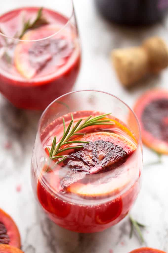 Elegant, ruby red cocktail for any daytime occasion. Blood Orange Rosemary Mimosa thekitchengiril.com #mimosa #bloodorange #cocktail #sparklingwine #prosecco #brunch #brunchcocktail #champagne
