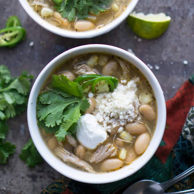 Throw-and-go (NO precook) crockpot recipe with JUICY chicken results! Easy Slow Cooker White Chicken Chili for busy weeknights! thekitchengirl.com #slowcookerchili #crockpotchili #whitechickenchili #slowcooker #crockpot #chili #whitechili #glutenfree