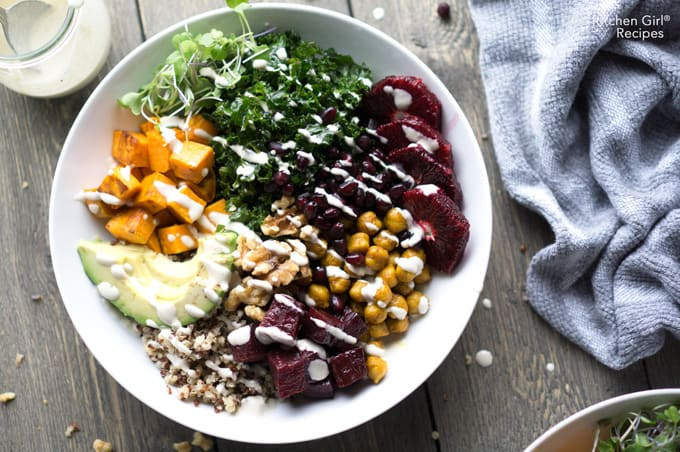 Superfood nourish bowl with chickpeas, kale, avocado, blood orange, sweet potato, pomegranate, beets, quinoa, sprouts, and walnuts. Turmeric Chickpea Beetroot Hippie Bowl with Lemon Tahini Dressing on thekitchengirl.com #buddhabowl #hippiebowl #nourishbowl #mealprep #superfood #veganbowl