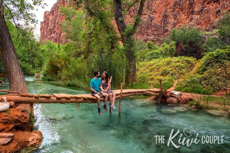 Rachel and Jeremy sitting on a bridge over clear blue water in The Grand Canyon, Havasupai