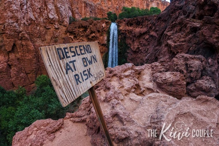 Sign that reads descend at your own risk on the edge of a cliff in Havasupai