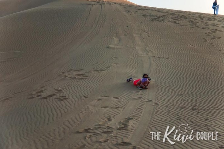 Rachel on a sand board, flying down the dunes of Huacachina