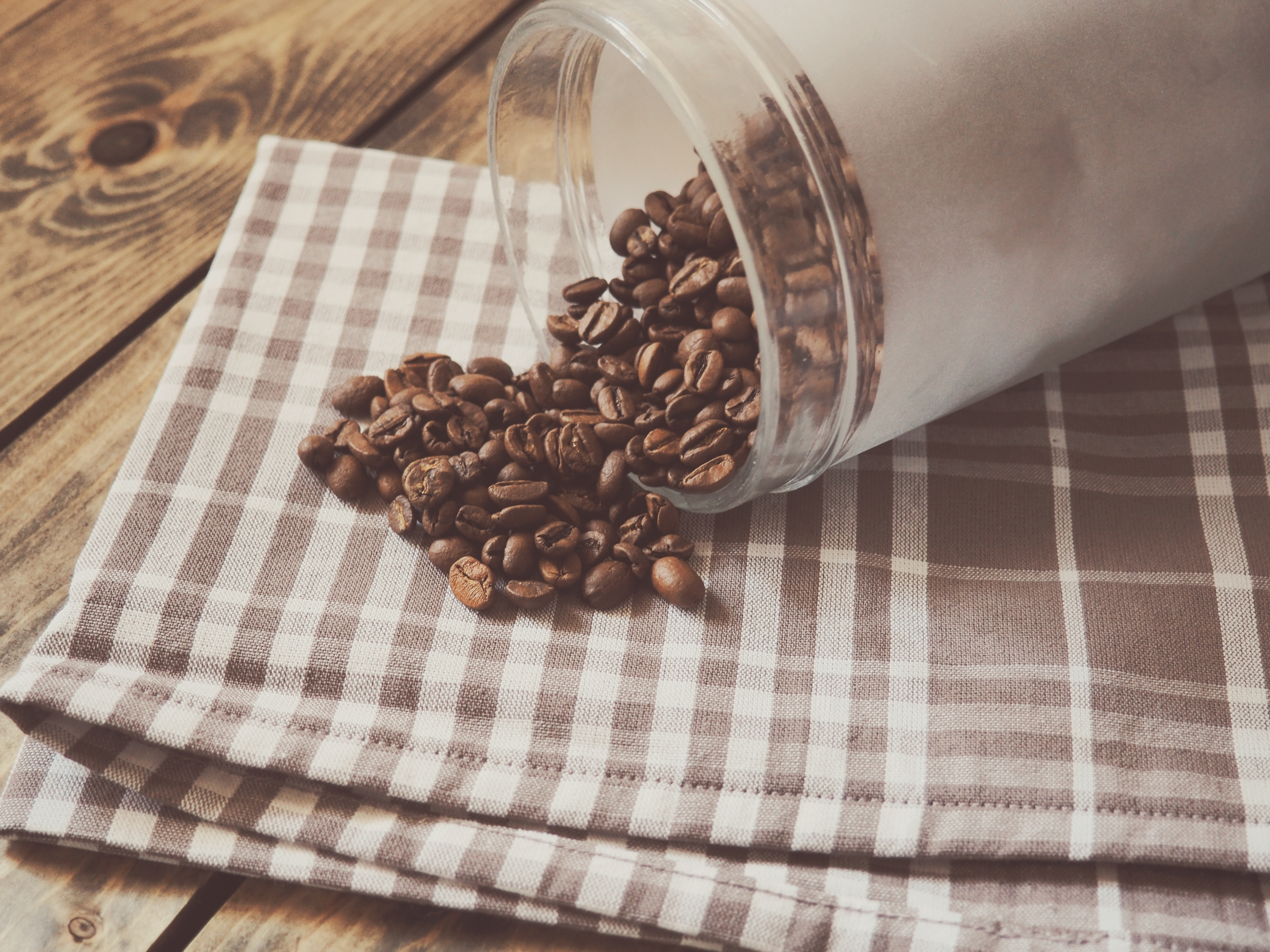 Coffee beans pour out of a white cup onto a checked cloth on a wooden floor.