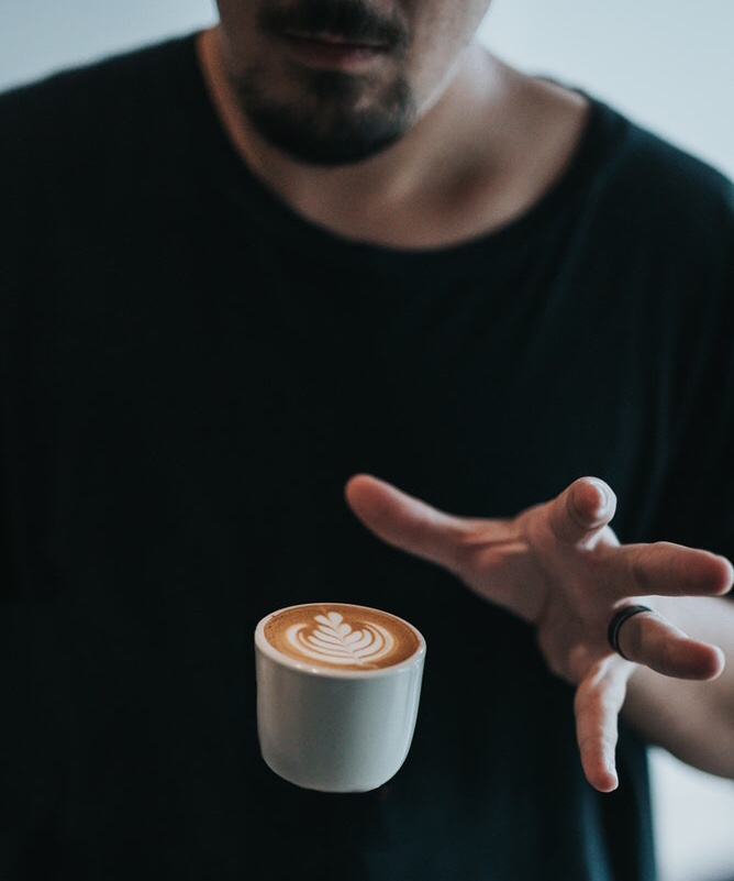 A person in a black shirt holds their hand over a latte that appears to be hovering.