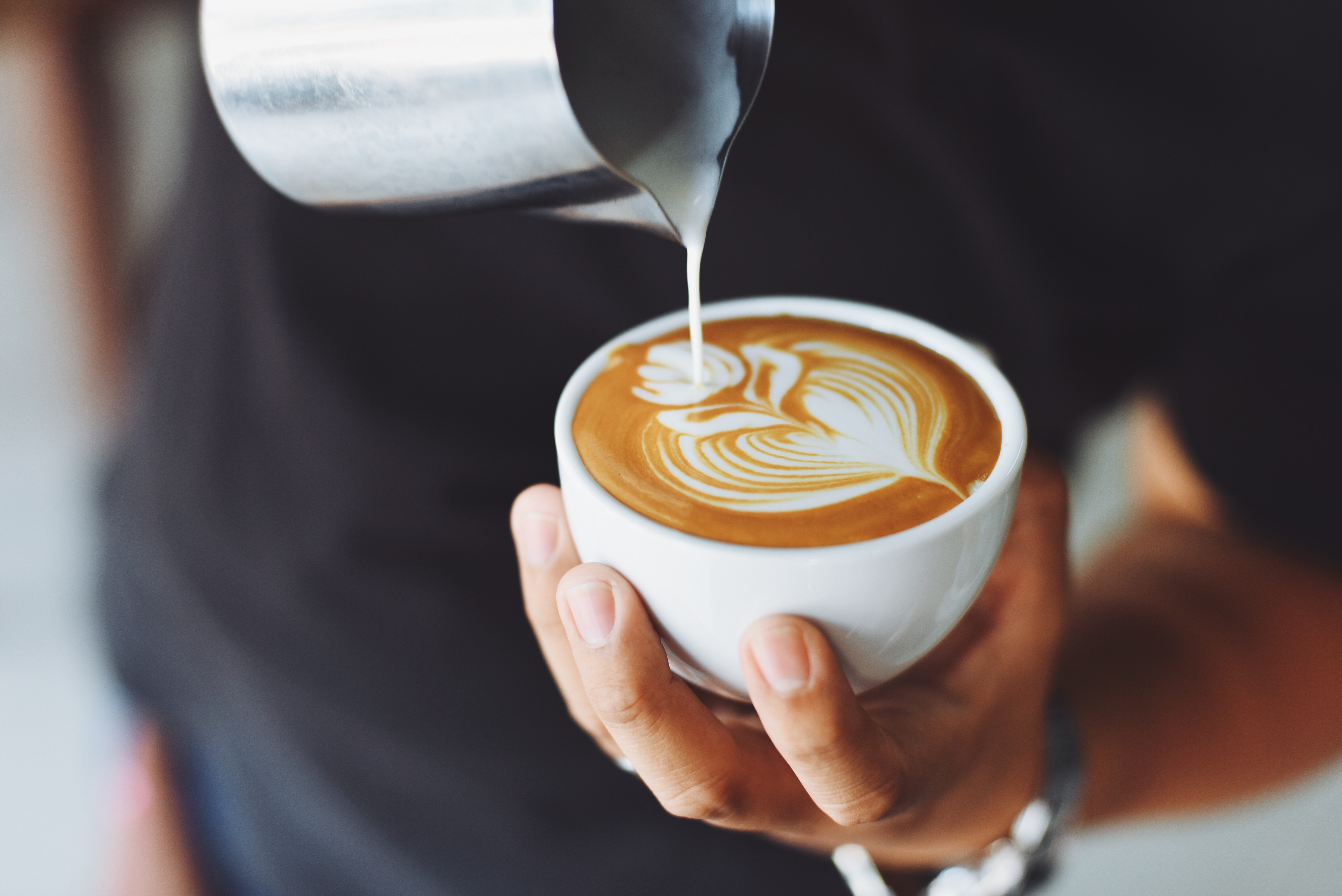 A barista holds a white cappuccino cup and pours perfectly textured milk into espresso.