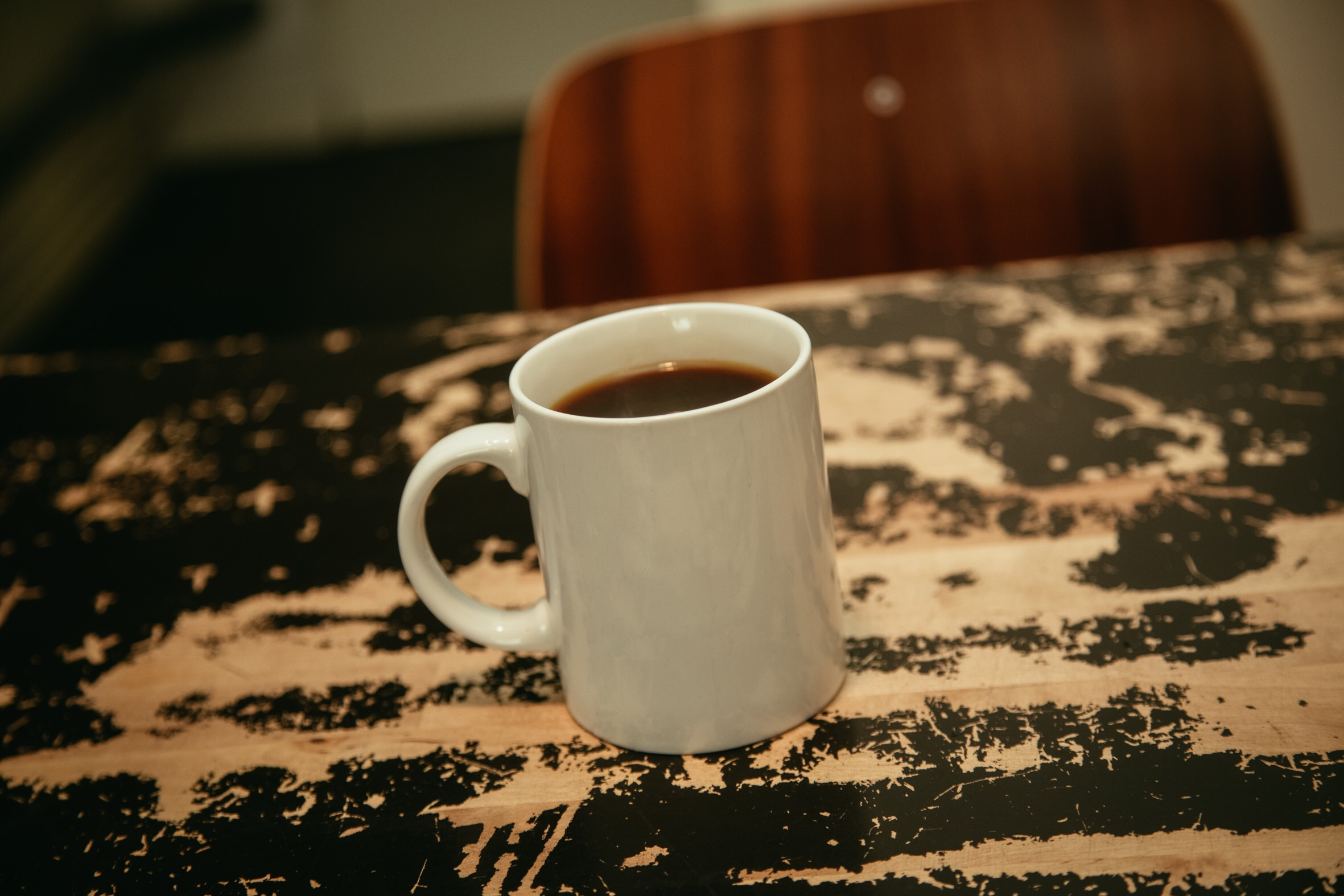A white mug of filter coffee on a wooden table.