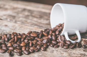 A wooden table with coffee beans spilling out of a white mug.