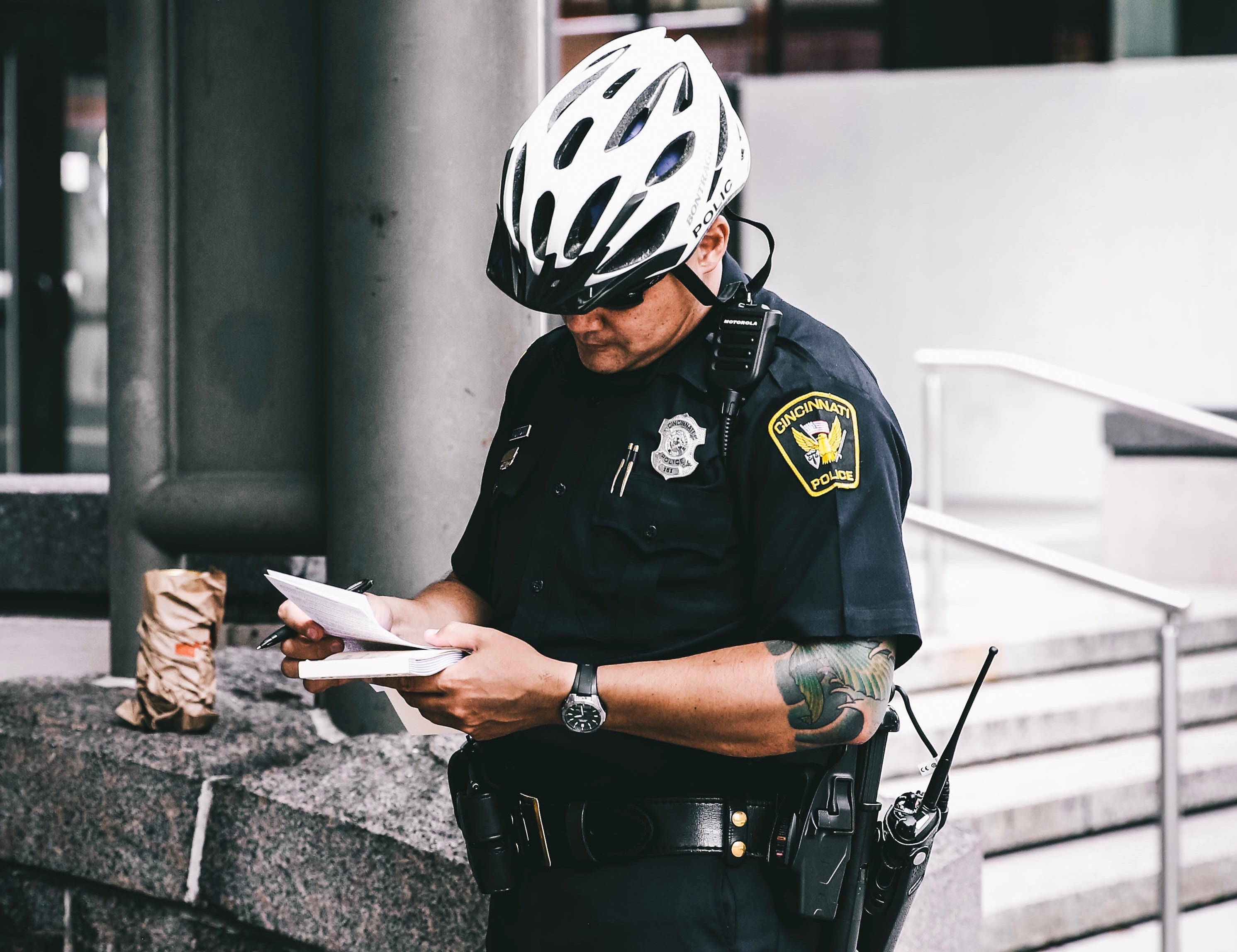 A police officer in a bike helmet with a coffee.