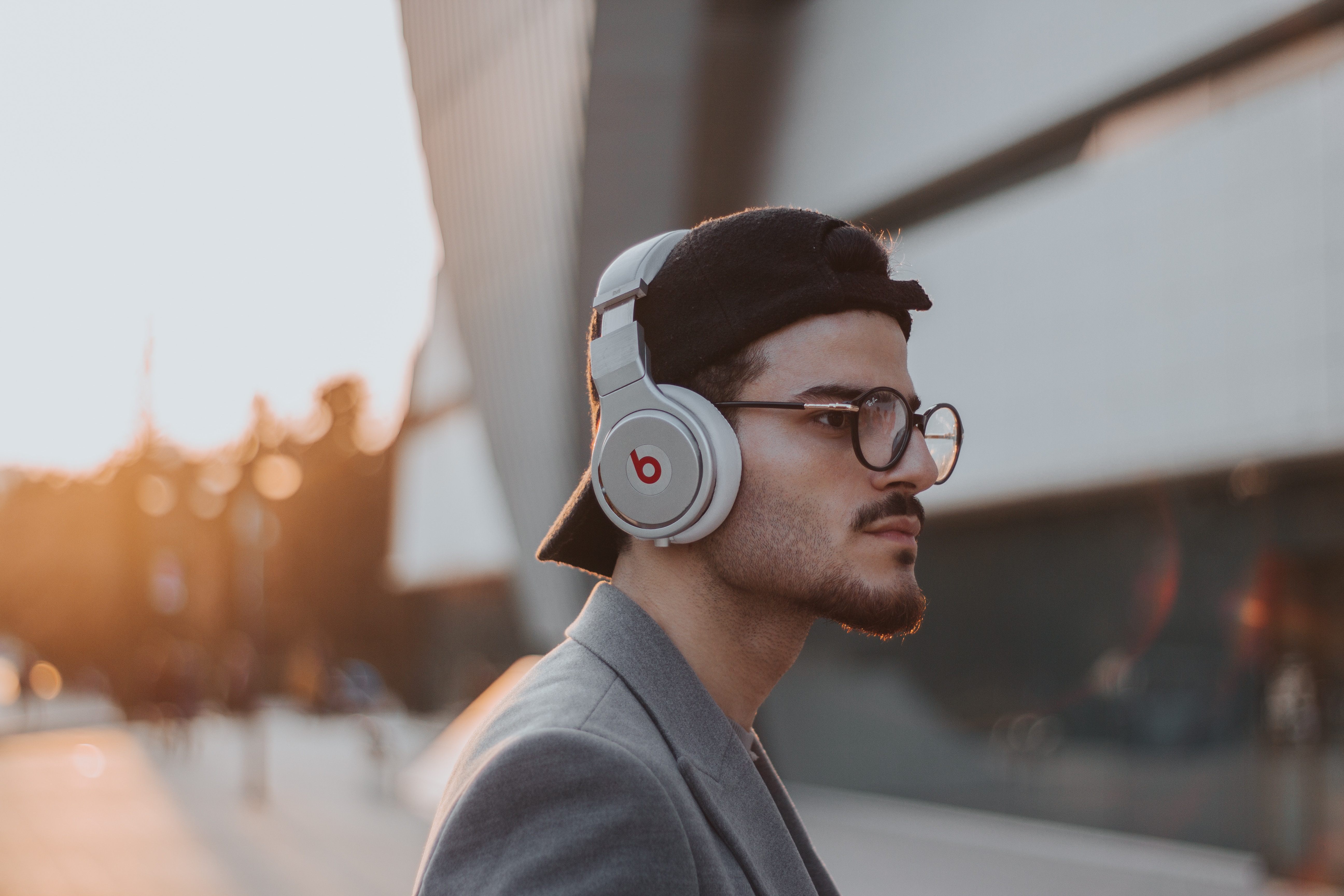 A man with headphones and a baseball cap.