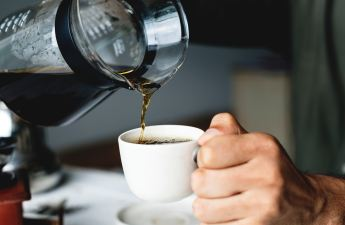 A person pours coffee from a glass carafe into a white coffee cup.