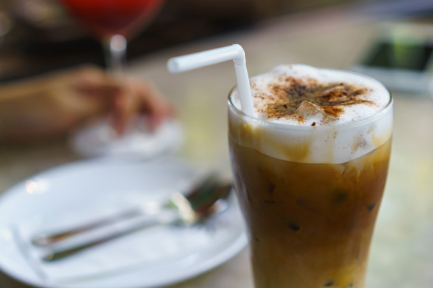 An iced cappuccino with a straw.
