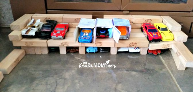 Girls play HotWheels, with a garage made with Jenga blocks