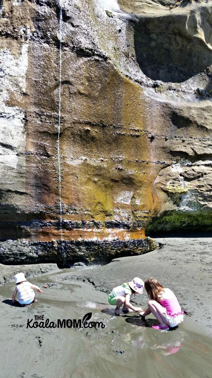 Three girls building a dam in a stream at Mystic Beach