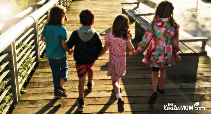 Four friends skipping along the sidewalk