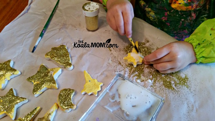 Jade adding glue and glitter to her salt dough magnets and ornaments.