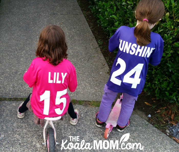 Girl on bike wearing a pink sports team jersey and girl on a scooter wearing a purple sports team jersey