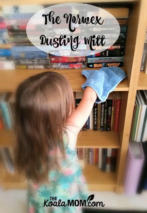 Toddler dusting bookshelves with the Norwex dusting mitt