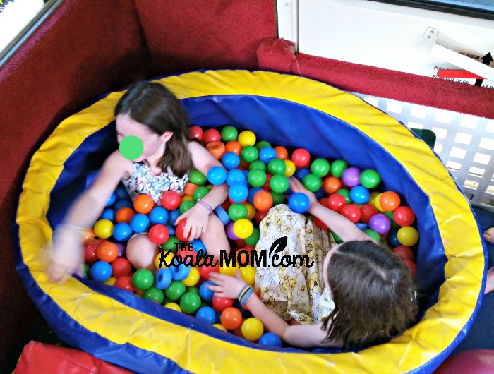 Sunshine and Lily in the ball pit on the Tumblebus
