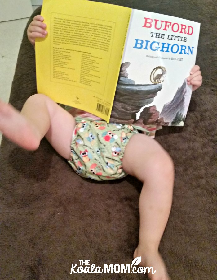Omaiki cloth diaper on a baby reading a Bill Peet book