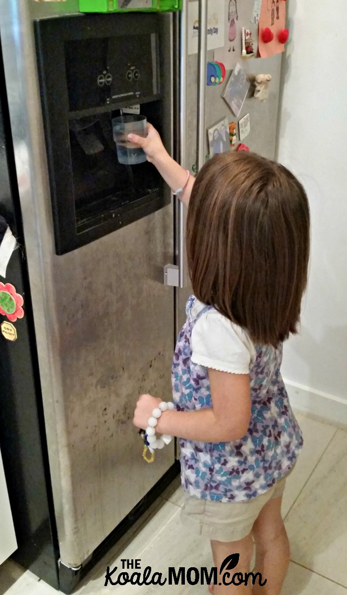4-year-old Jade getting water for herself at the fridge.