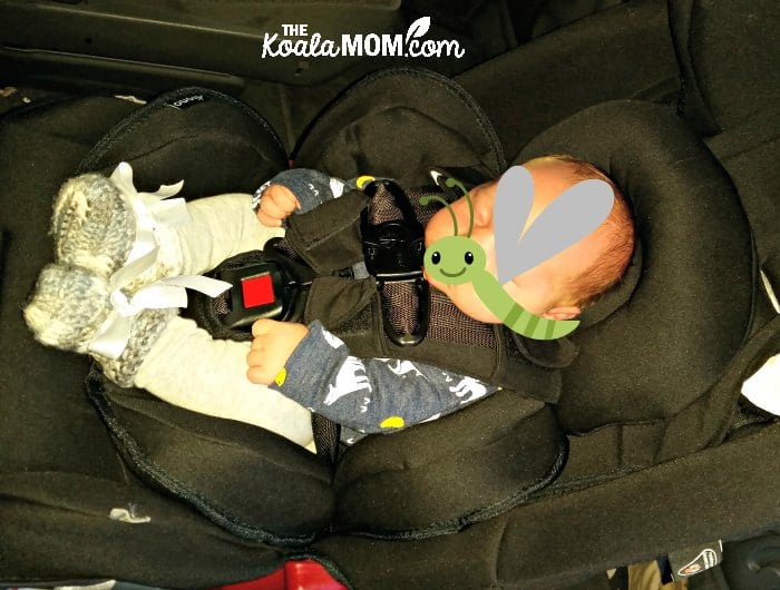 Infant sitting cozily in a Diono Radian car seat, supported by the infant cushions