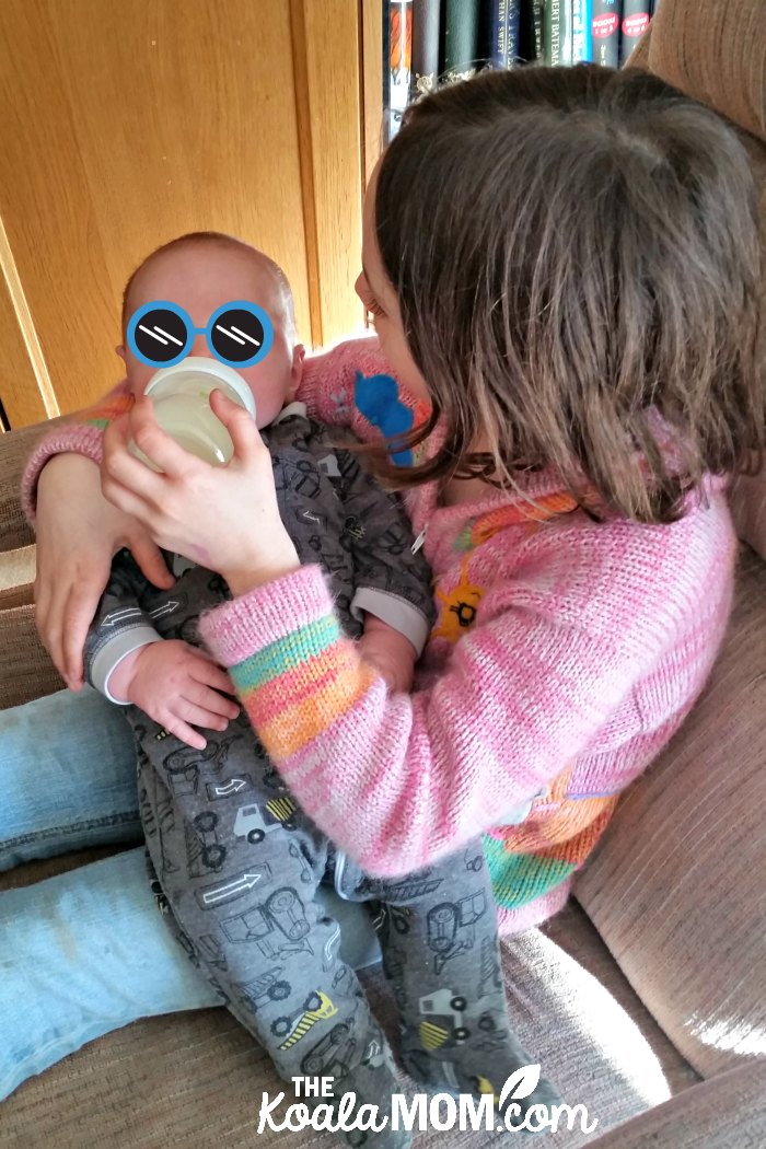 Big sister feeding her 2-month-old brother with the Nuk Simply Natural bottle