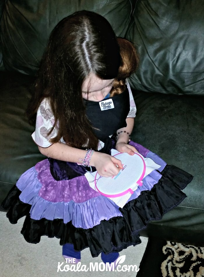 Nine-year-old girl wearing her 18-inch doll in a Beluga Baby bamboo doll wrap while doing cross-stitch