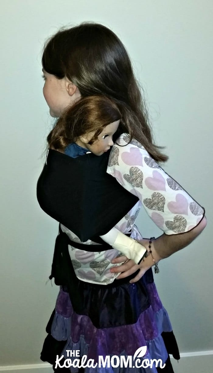 Nine-year-old girl wearing her 18-inch doll in a Beluga Baby bamboo doll wrap