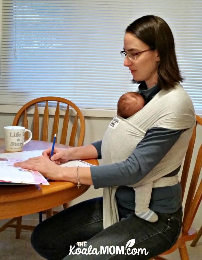 Homeschool mom going over lesson plans with baby wrapped in a Beluga Baby bamboo carrier.