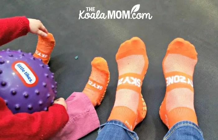 Mom and toddler wearing their orange SkyZone socks.