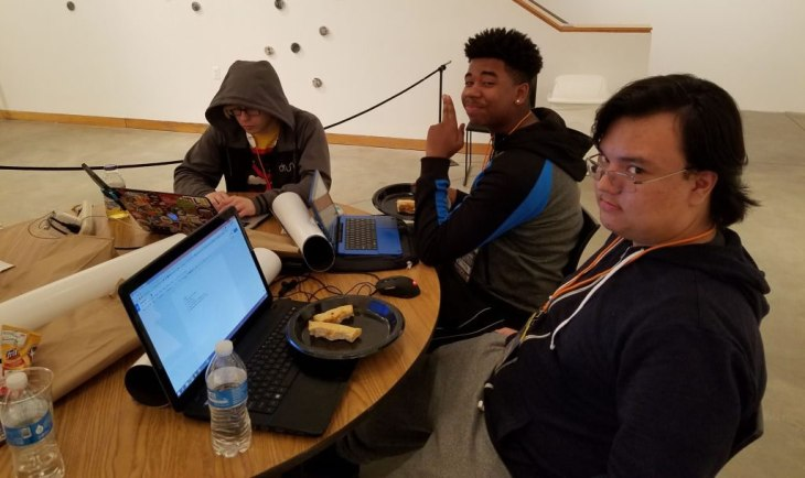 A picture of three people working at a game jam