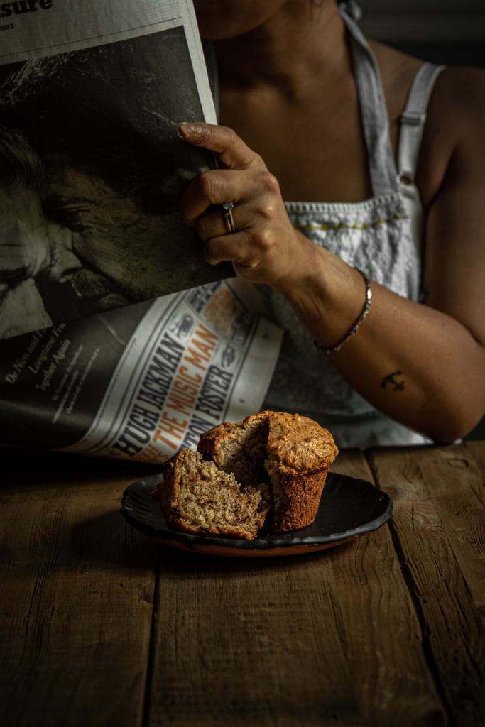 woman reading newspaper behind a muffin on a brown plate
