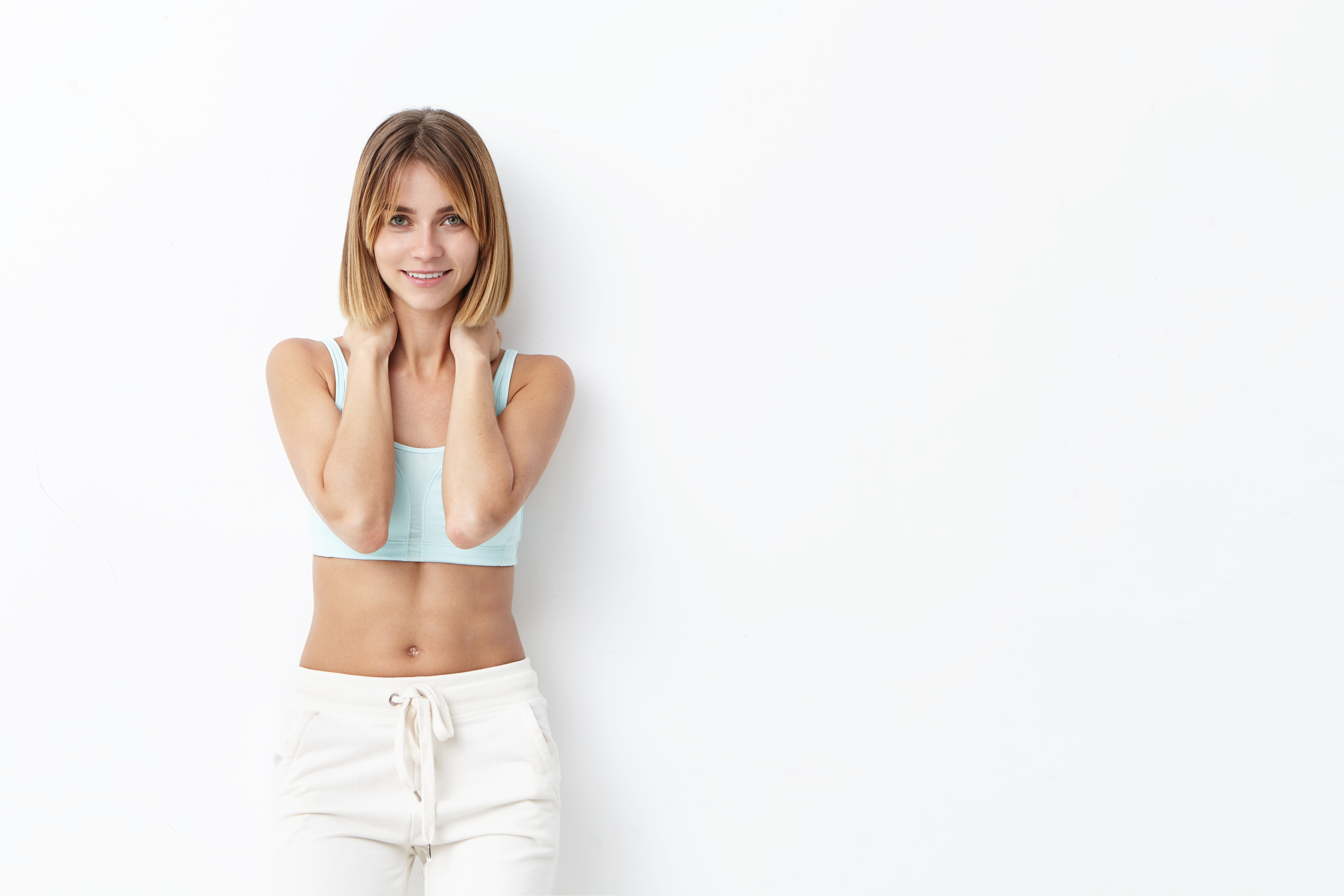Female sport trainer with slim body, dressed in sport clothes, keeping hands on neck, having happy expression while waiting for her pupils. Athletic woman going to run, isolated over white wall
