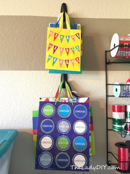 Spray paint Command hooks and hang gift bags as part of a simple, DIY gift wrap storage solution.