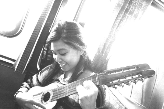 The camera is turned around on photographer Jan Hilario as she plays the charango, an Andean string instrument.