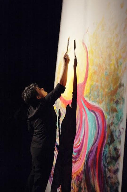 Artist NikNaz painting Survive at an event called Anu.