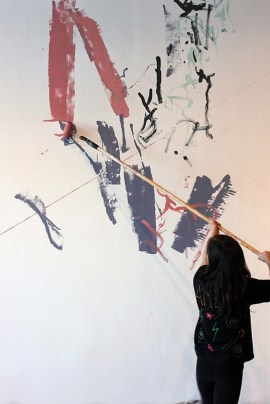 Amelie goes big with a paint roller during an art-making session.   Photo by Valerie Salez