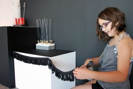 Isabelle uses a staple gun to put finishing touches on her sculpture installation.   Photo by Valerie Salez