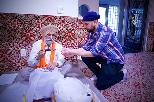 Pall Singh-Beesla receiving an offering of Karah Parshad, a sacred pudding of the Sikh faith. | Photo by Danny Kresnyak