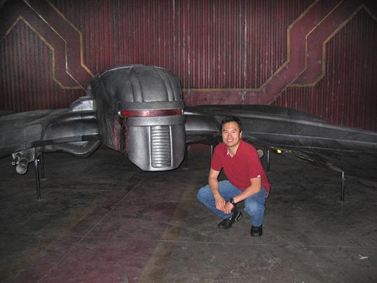 Film designer Eric Chu next to a full-size Cylon Raider from Battlestar Galactica. | Photo courtesy of Eric Chu.