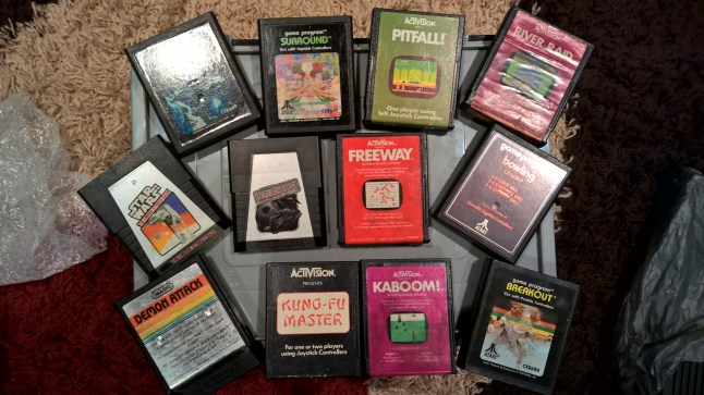 Loose 2600 cartridges including Pitfall!, River Raid and The Empire Strikes Back. Top left cartridge (obscured) is Asteroids.