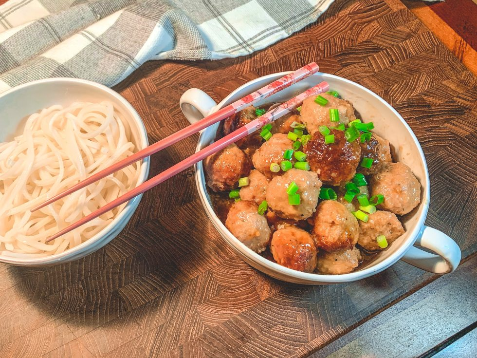 Chicken meatballs in a white bowl accompanies by rice noodles