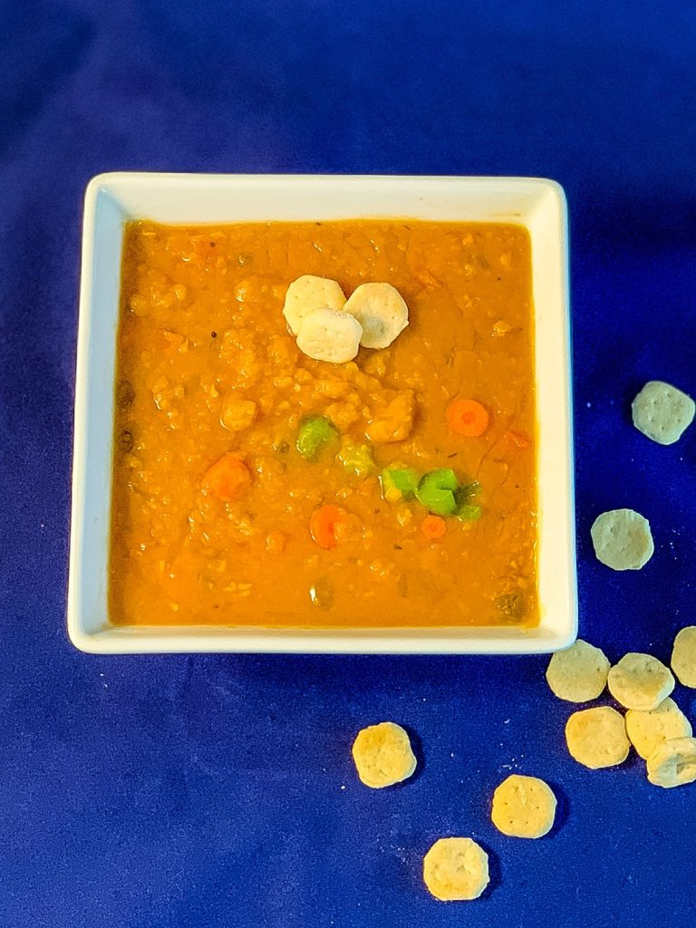 Top view of slow cooker split pea soup made with yellow split peas and garnished with some oyster crackers
