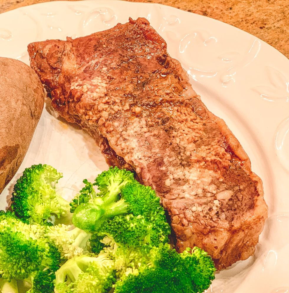 Cooked steak with garlic on top, broccoli and potato all on a white plate.