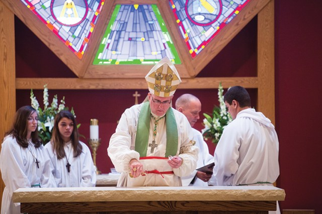 Archbishop Joseph F. Naumann anoints the new altar at Sacred Heart Church in Sabetha with chrism oil on Oct. 13.